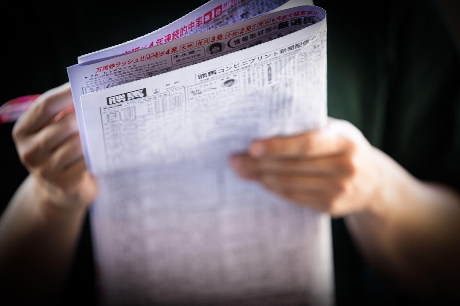 競馬新聞 手に持つ人